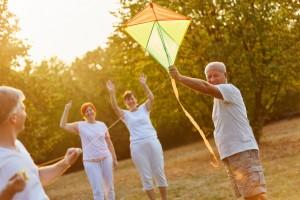 Senioren haben Spaß beim Drachen steigen in der Natur im Herbst